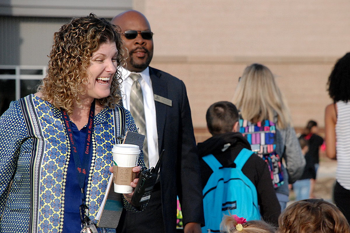 Principal Carrie Clark, left, and Superintendent Rico Munn greet students at the Edna and John W. Mosley P-8 school Monday, the first day of school for most students at the new school.