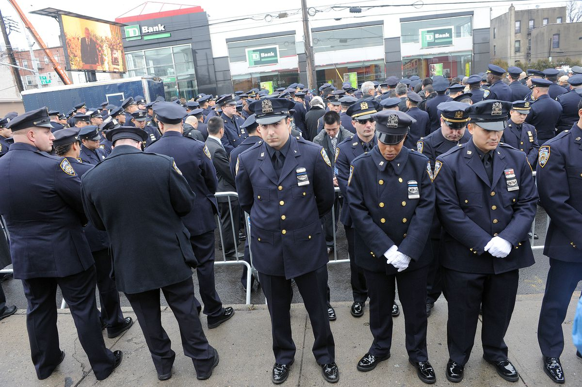 NYPD officers turn their backs on Mayor Bill de Blasio in protest during the funeral for NYPD officer Wenjian Liu in 2014.