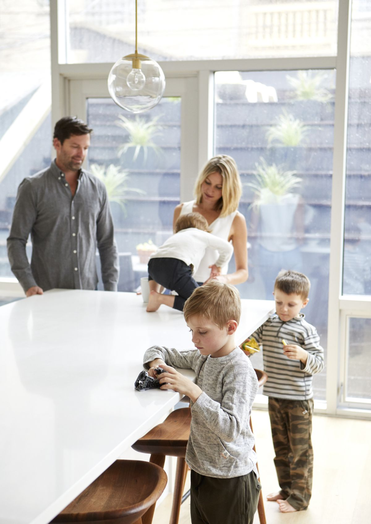 The couple and their kids pose in the white kitchen.