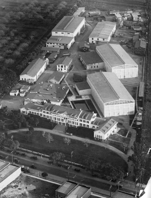 Black and white aerial view of a studio lot. A sprawling mansion is positioned in front of a half dozen low-rise buildings.