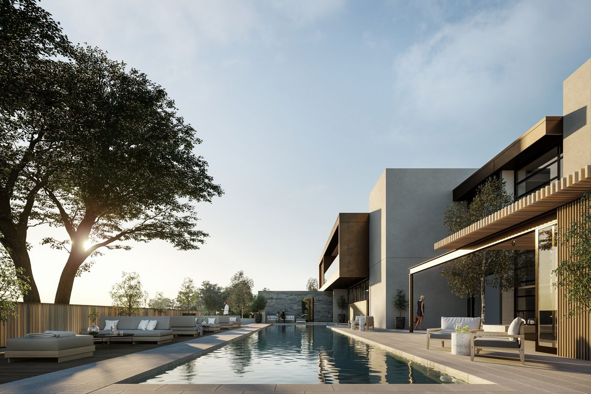 A lap pool with lounge seating next to a two-story fancy building.