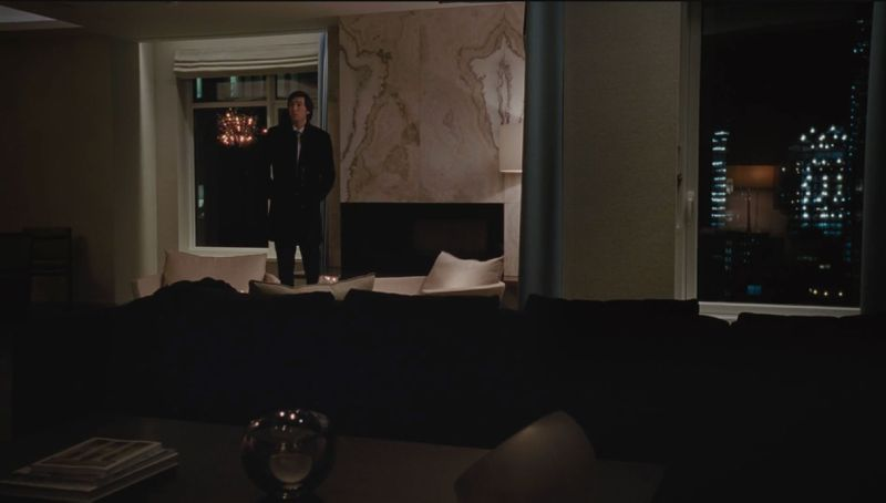 A man stands in a large living room in the HBO show Succession. The wall behind him is marble. The room is dimly lit and there are floor to ceiling windows with a view of city buildings.