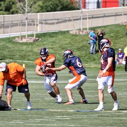 Broncos QB Chad Kelly (6) hands off to FB Andy Janovich while fellow QBs Case Keenum (4) and Paxton Lynch (12) look on.
