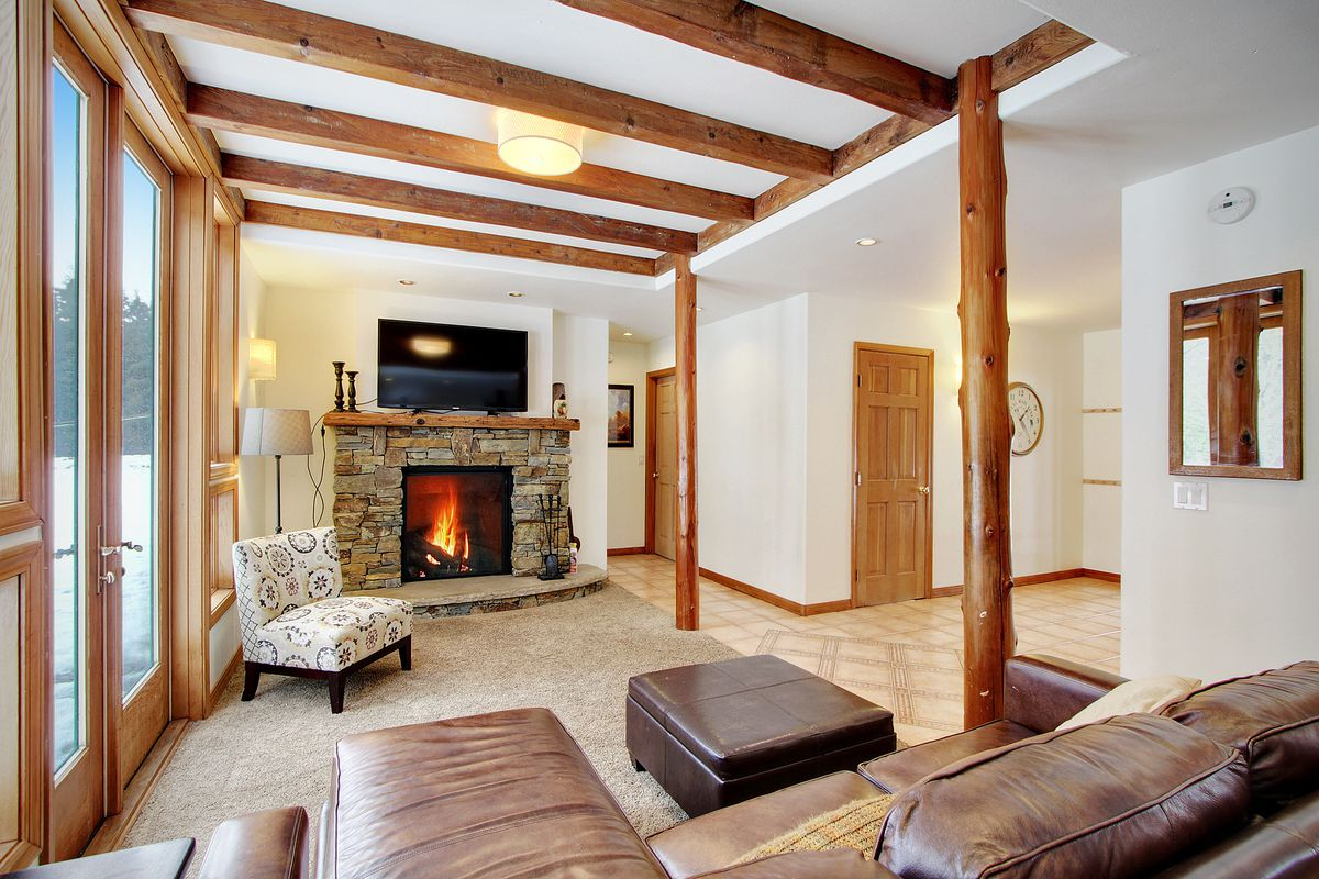 A living room with exposed ceiling beams, French doors and a stone fireplace