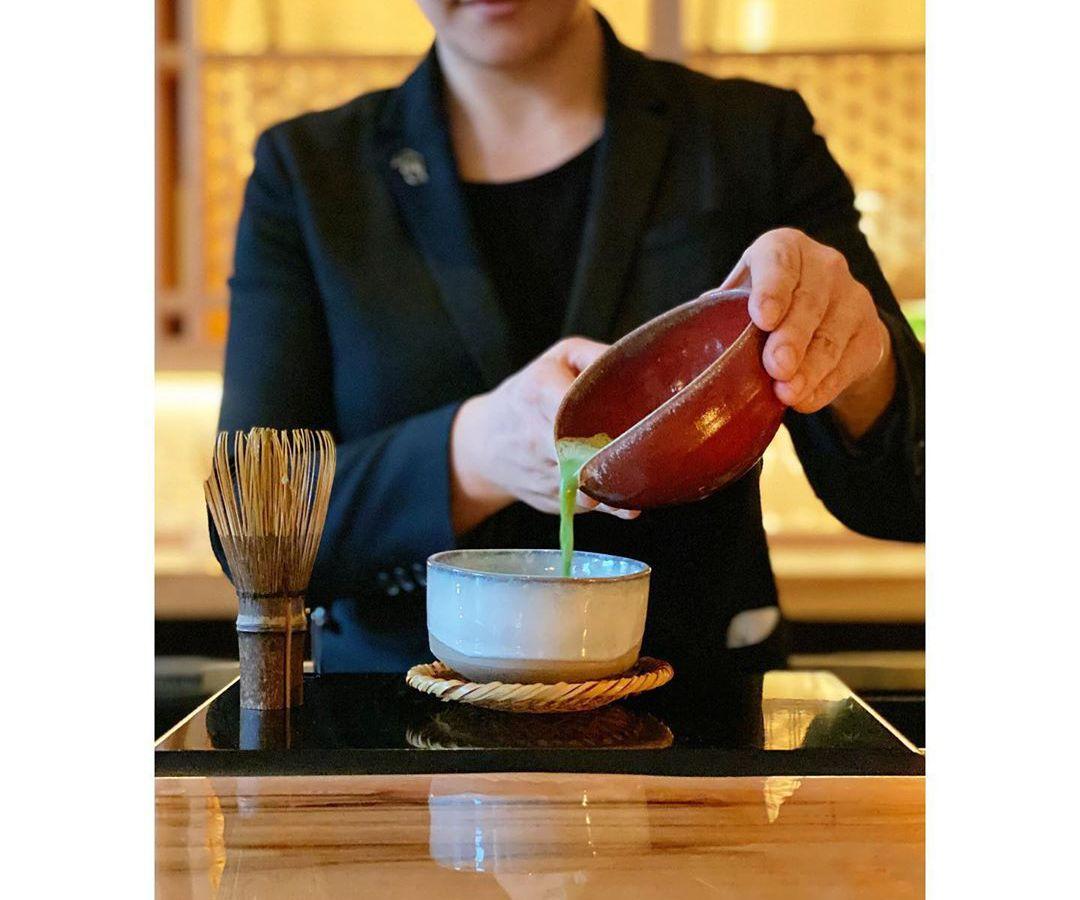 A woman pouring matcha into a bowl.