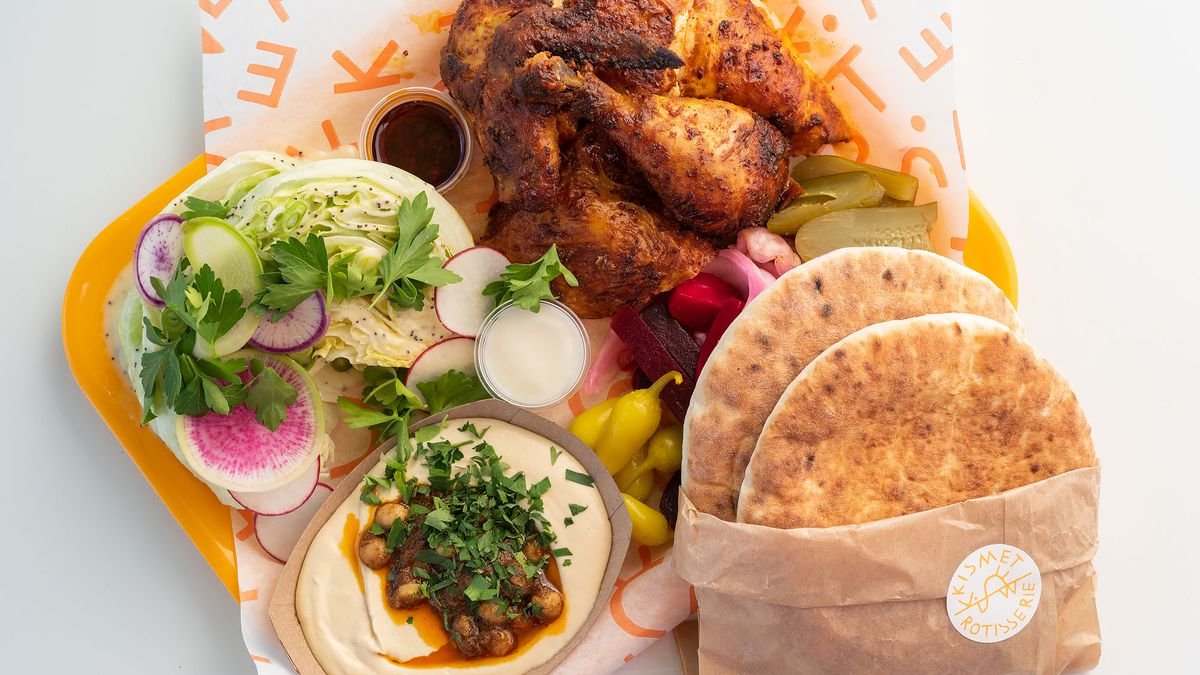 A plate of rotisserie chicken with hummus and a side salad and pita on a yellow tray.