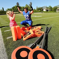 Utah Falconz Stephanie Crosland signals a touchdown with her daughter Brooklyn after a game with the Colorado Freeze in Murray on June 13, 2015. The Falconz compete in a women's tackle football league.