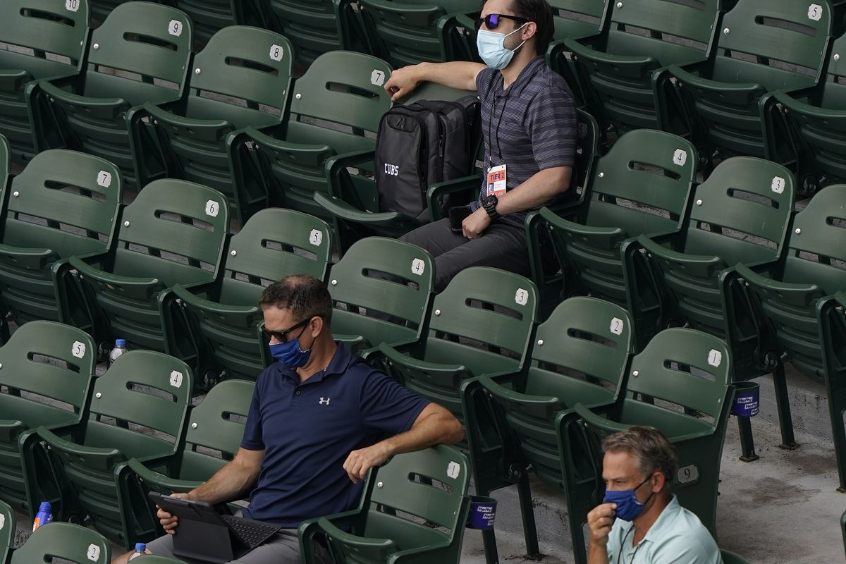 Theo Epstein president of baseball operations for the Chicago Cubs and Jed Hoyer executive vice-president and general manager watching the game between the Chicago Cubs and the Milwaukee Brewers at Wrigley Field on July 25, 2020 in Chicago, Illinois.