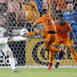 Real Salt Lake midfielder Albert Rusnak, left, attempts a shot on goal as Houston Dynamo midfielder Matias Vera (22) defends and Teenage Hadebe (18) and goalkeeper Marko Maric (1) look on during the second half of an MLS soccer match Saturday, July 31, 2021, in Houston.