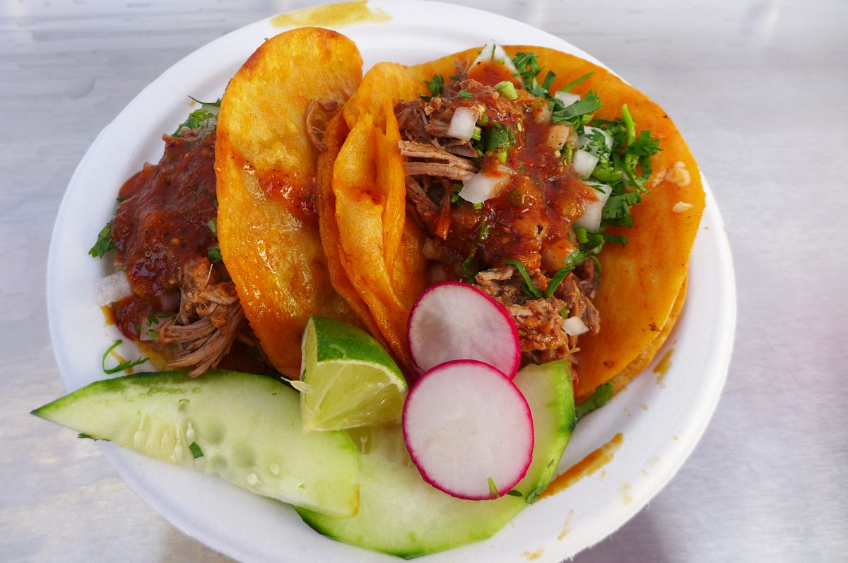 A pair of tacos filled with reddish meat and sided with cucumbers and radishes.