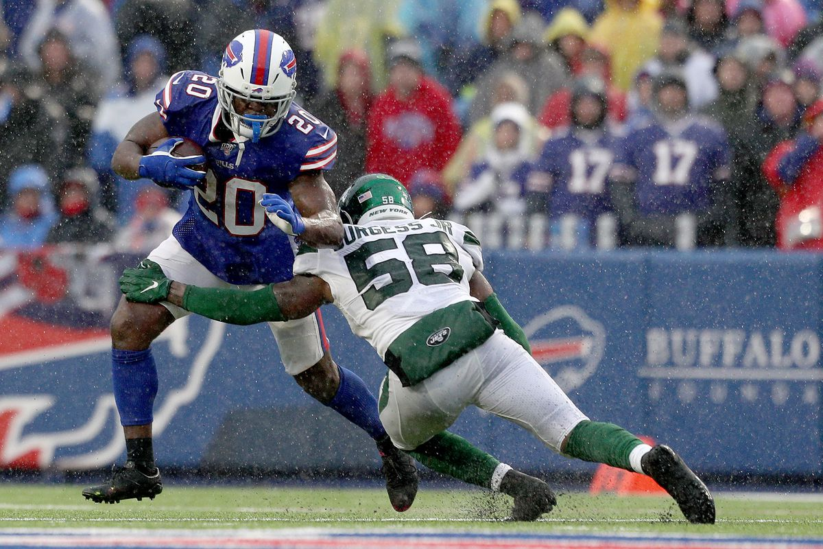 Frank Gore of the Buffalo Bills runs with the ball as James Burgess of the New York Jets attempts to tackle him during the second quarter of an NFL game at New Era Field on December 29, 2019 in Orchard Park, New York.