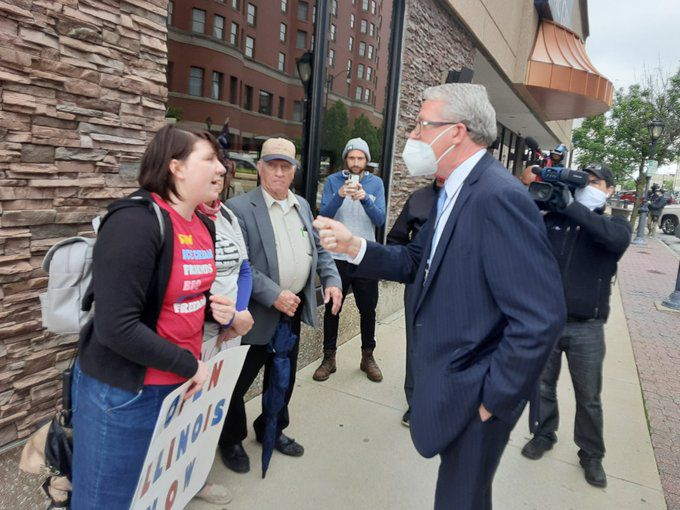House Republican Leader Jim Durkin confronts protester Brittany Emel about her sign comparing Gov. J.B. Pritzker to Adolf Hitler outside the Bank of Springfield Convention Center in May.