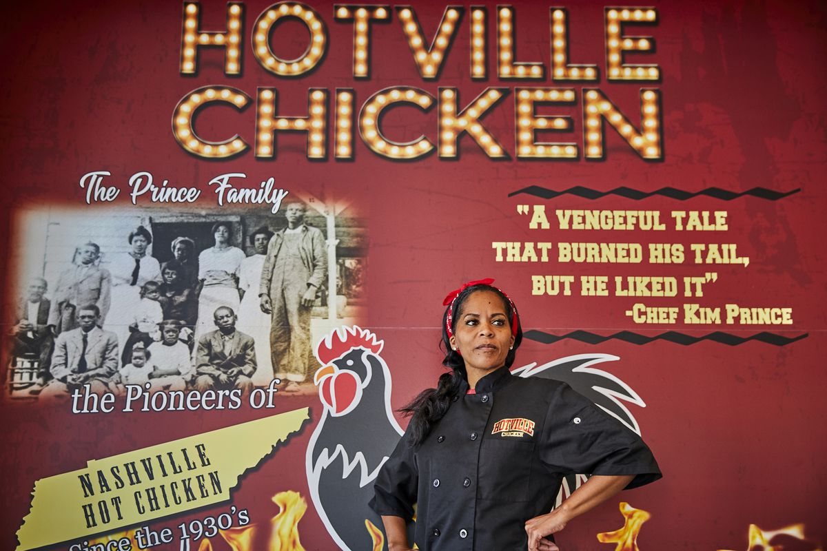 Hotville Chicken owner Kim Prince stands confidently in front of a banner in the restaurant's LA location.