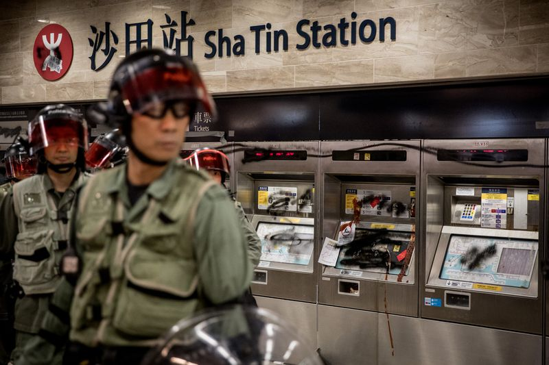 Hong Kong police stand in front of vandalized ticket machines.