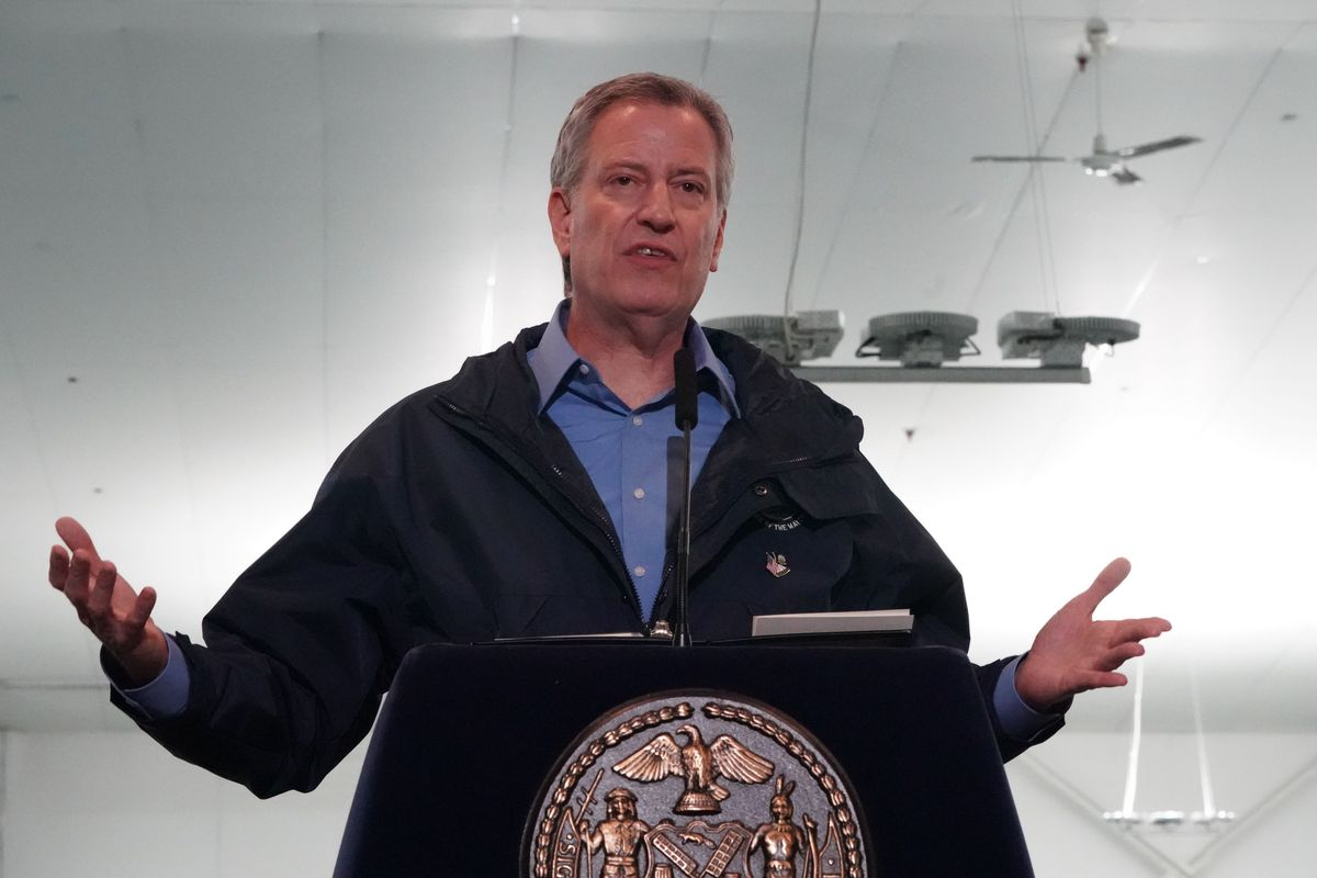 NYC Mayor Bill de Blasio behind a podium, announcing more temporary hospital facilities at a press conference