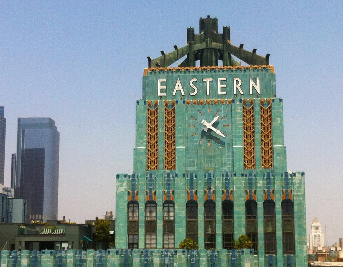 The exterior of the Eastern Columbia Lofts in Los Angeles. The facade is green with a white sign that reads: Eastern. There is a clock on the building. There are orange decorative flourishes.