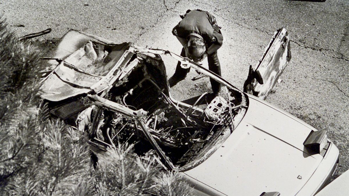 A police officer searches Mark Hofmann's car after a bomb exploded in it, injuring Hofmann on Oct. 16, 1985.