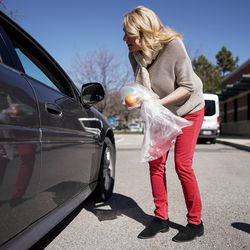 Lisa Schofield, manager at the Liberty Senior Center in Salt Lake City, delivers a packed lunch to a waiting car at the center on Tuesday, March 17, 2020. Senior centers are not allowing people to congregate for meals due to concerns over spreading COVID-19 but are instead letting seniors pick up their meals.