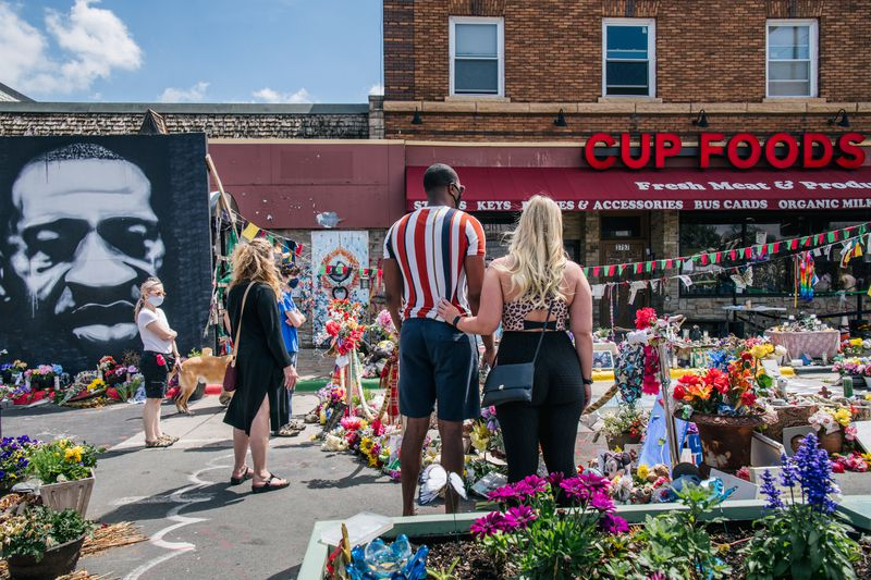 People pay their respects to George Floyd in the intersection of 38th Street and Chicago Avenue on May 25, 2021, in Minneapolis, Minnesota.