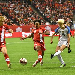 Rapinoe shoots past Canadian defenders Rebecca Quinn and Ashley Lawrence.