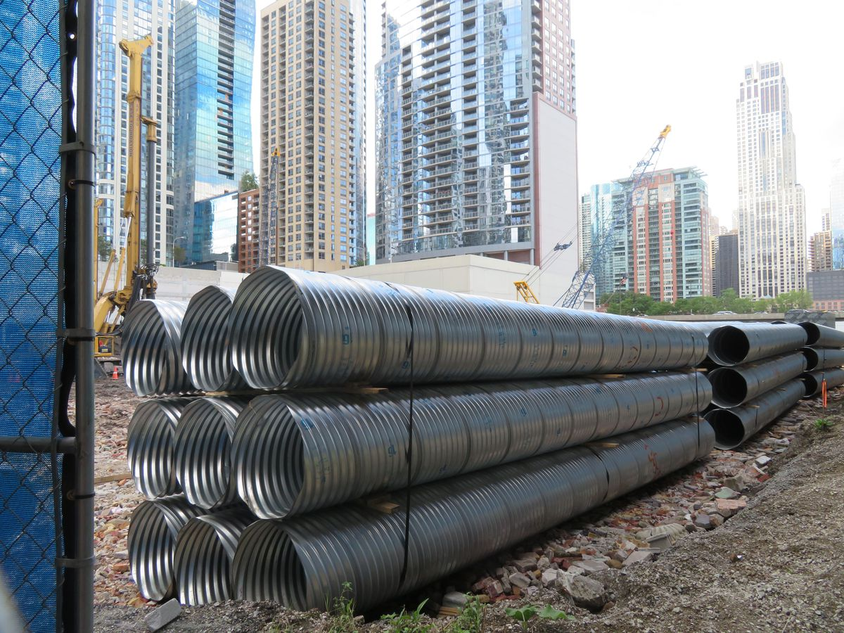 A stack of metal sleeves sit at the corner of a construction site. A row of taller buildings is visible beyond.