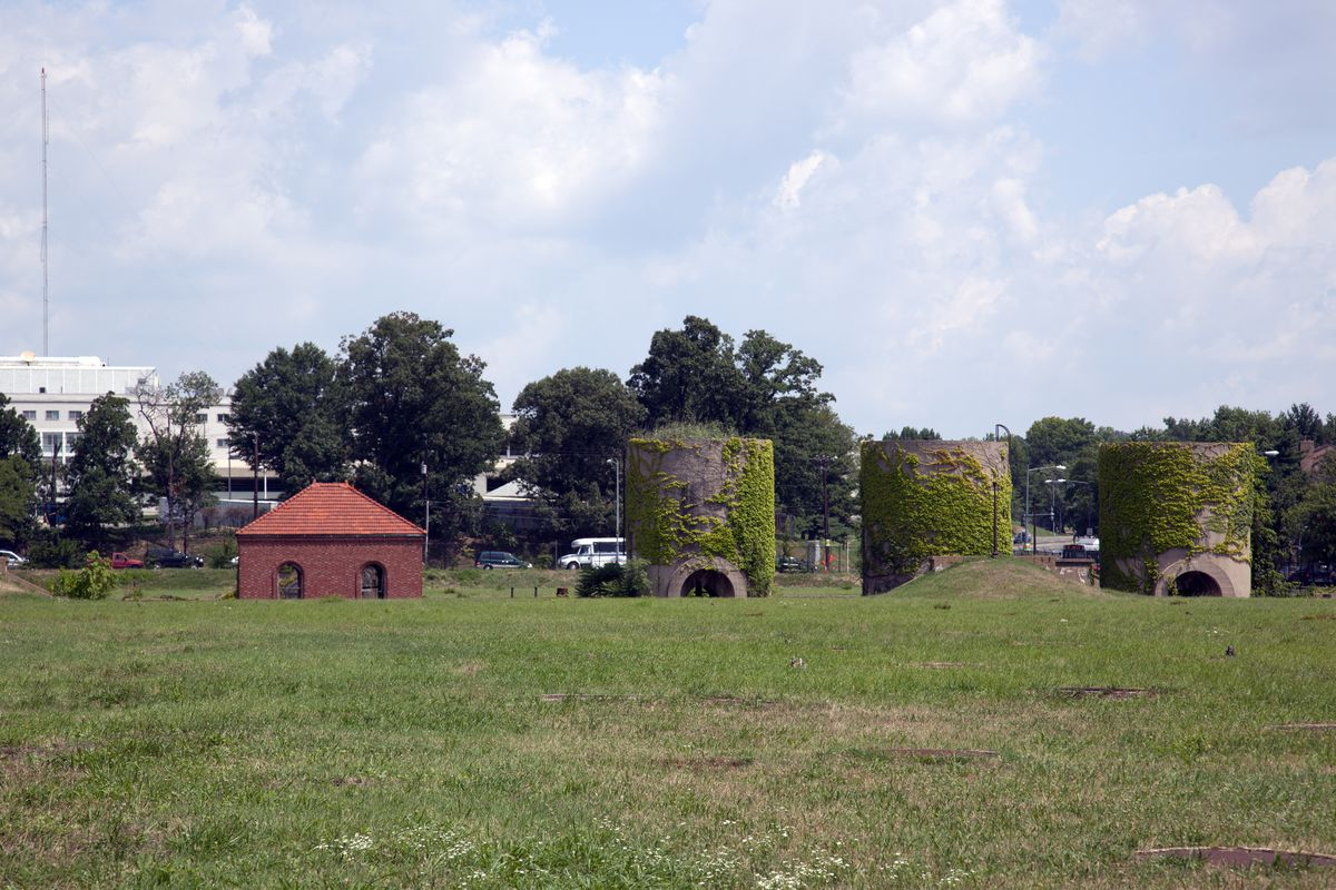 A set of sand silos in the middle of a green field.