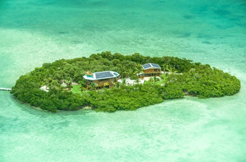 An aerial view of an island surrounded by turquoise water. You can see two homes with solar panels surrounded by vegetation.