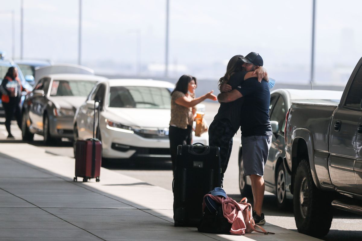 Anya Anderson, from Eden, embraces, her husband before departing for Russia outside of the Salt Lake airport.