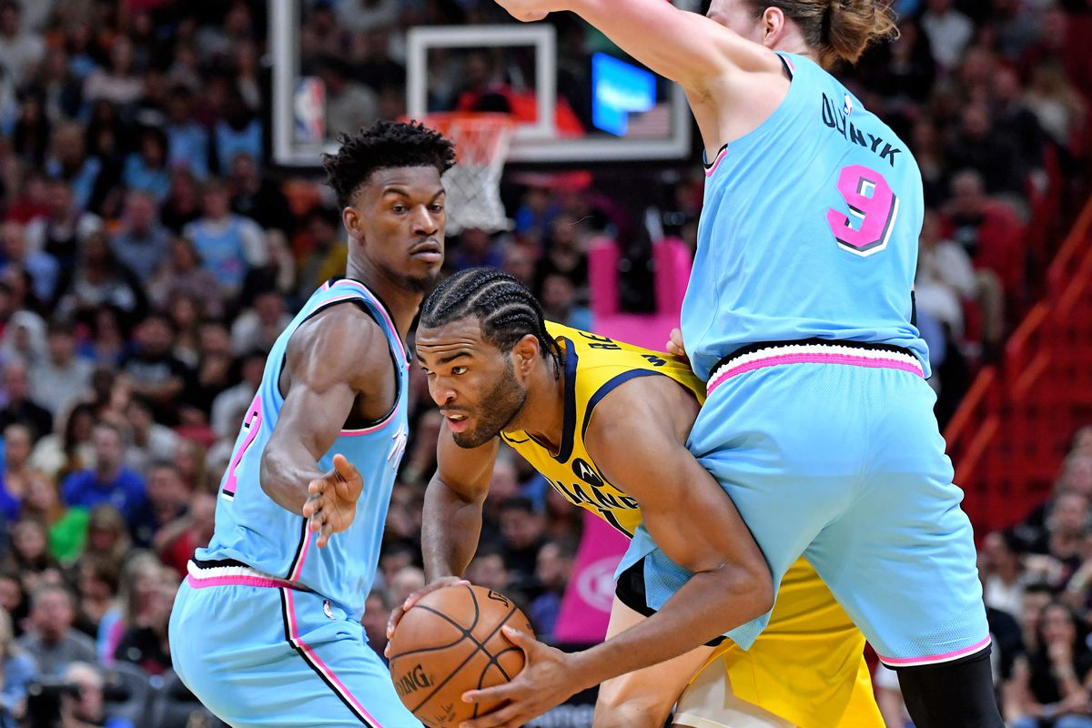 Indiana Pacers forward T.J. Warren is pressured by Miami Heat forward Kelly Olynyk and Miami Heat forward Jimmy Butler during the first half at American Airlines Arena.