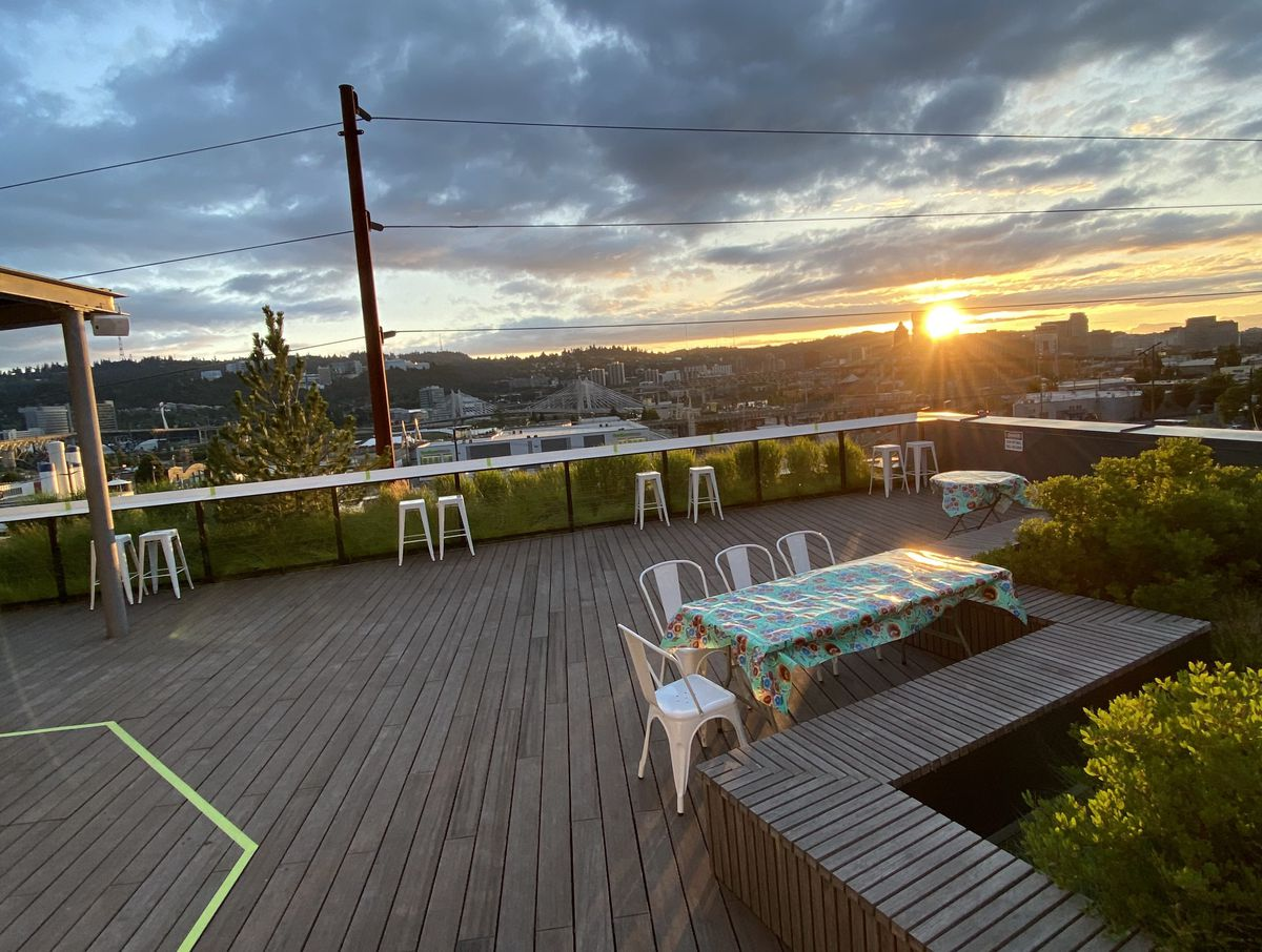 Sunset over a rooftop deck with a single large table and distanced stools