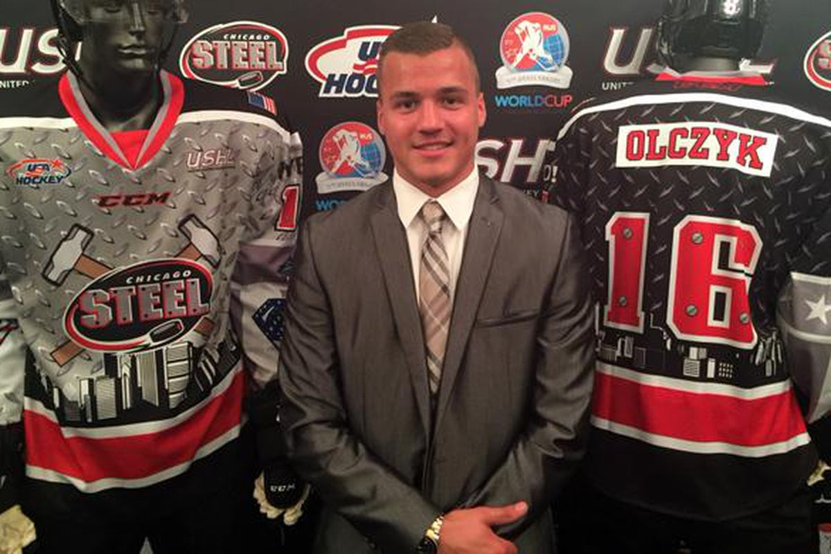 USHL Chicago Steel forward Nick Olczyk, son of Blackhawks TV analyst Eddie, stands next to the sweaters the Steel will wear at the Junior Club World Cup.