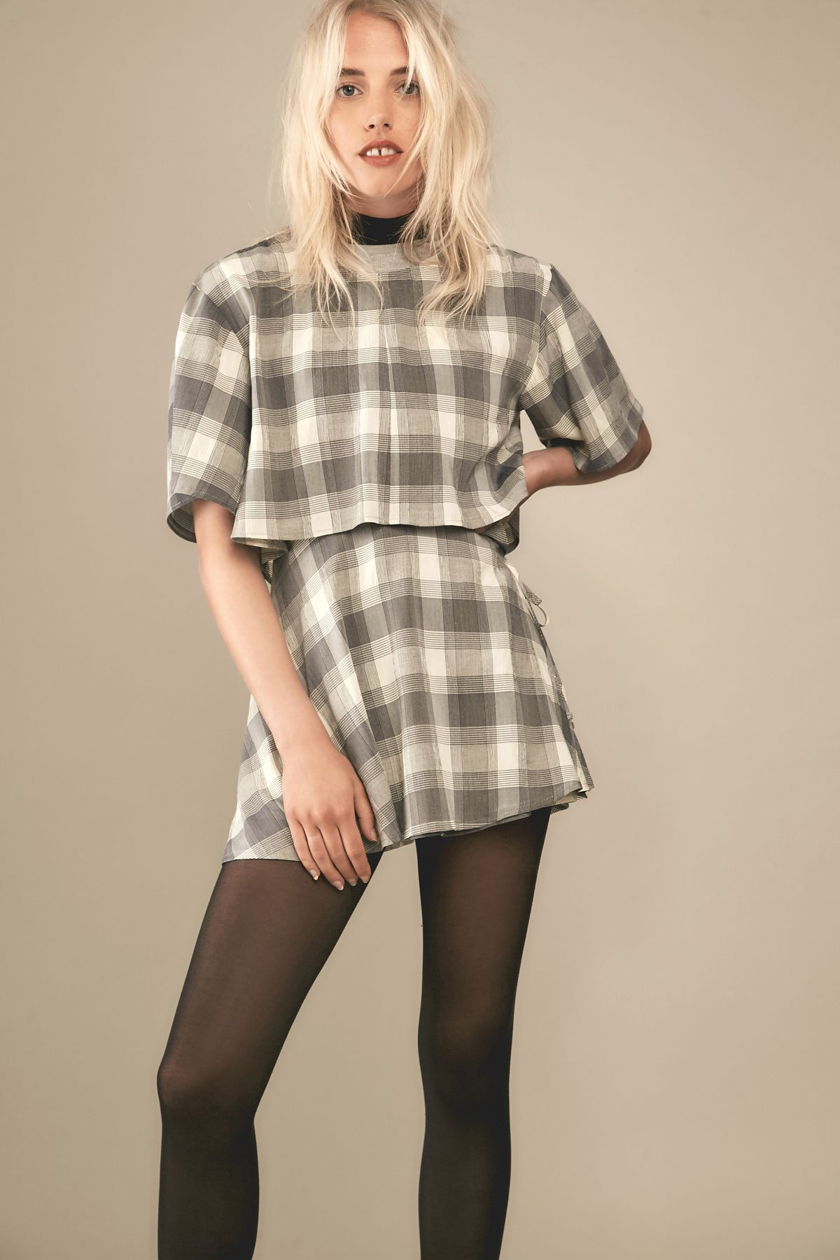 Blonde white model facing camera wearing plaid top and skirt with black tights