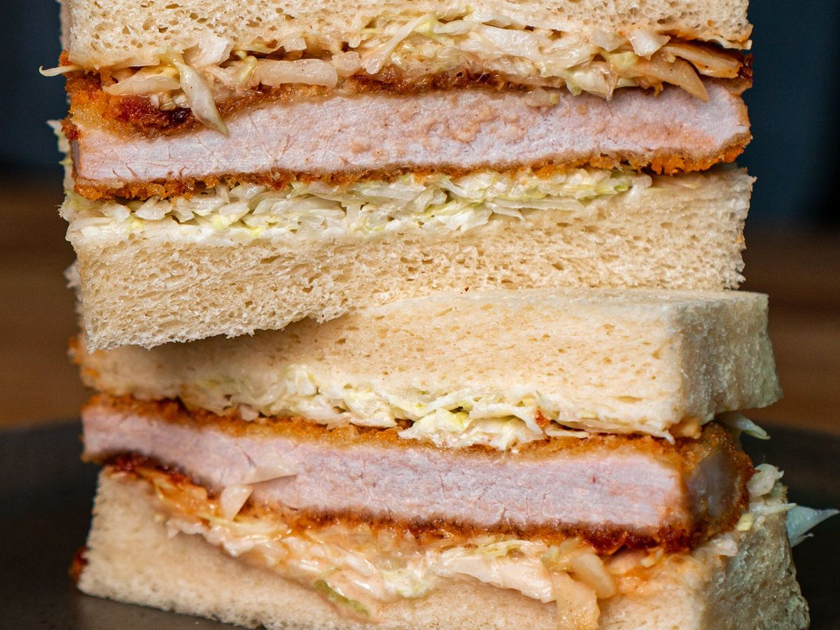 A sandwich made with shokupan — a Japanese milk bread — stuffed with crispy, golden brown pork katsu (deep fried pork cutlet)
