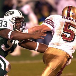"""<strong>2001</strong> """"San Francisco 49ers' quarterback Jeff Garcia (R) is sacked by the New York Jets James Reed (L)"""""""