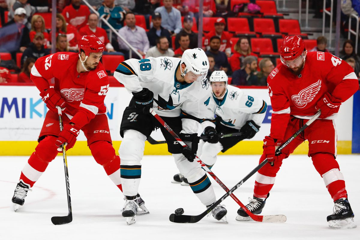 Jan 31, 2018; Detroit, MI, USA; Detroit Red Wings defenseman Jonathan Ericsson (52) San Jose Sharks center Tomas Hertl (48) and Detroit right wing Luke Glendening (41) battle for the puck in the first period at Little Caesars Arena.
