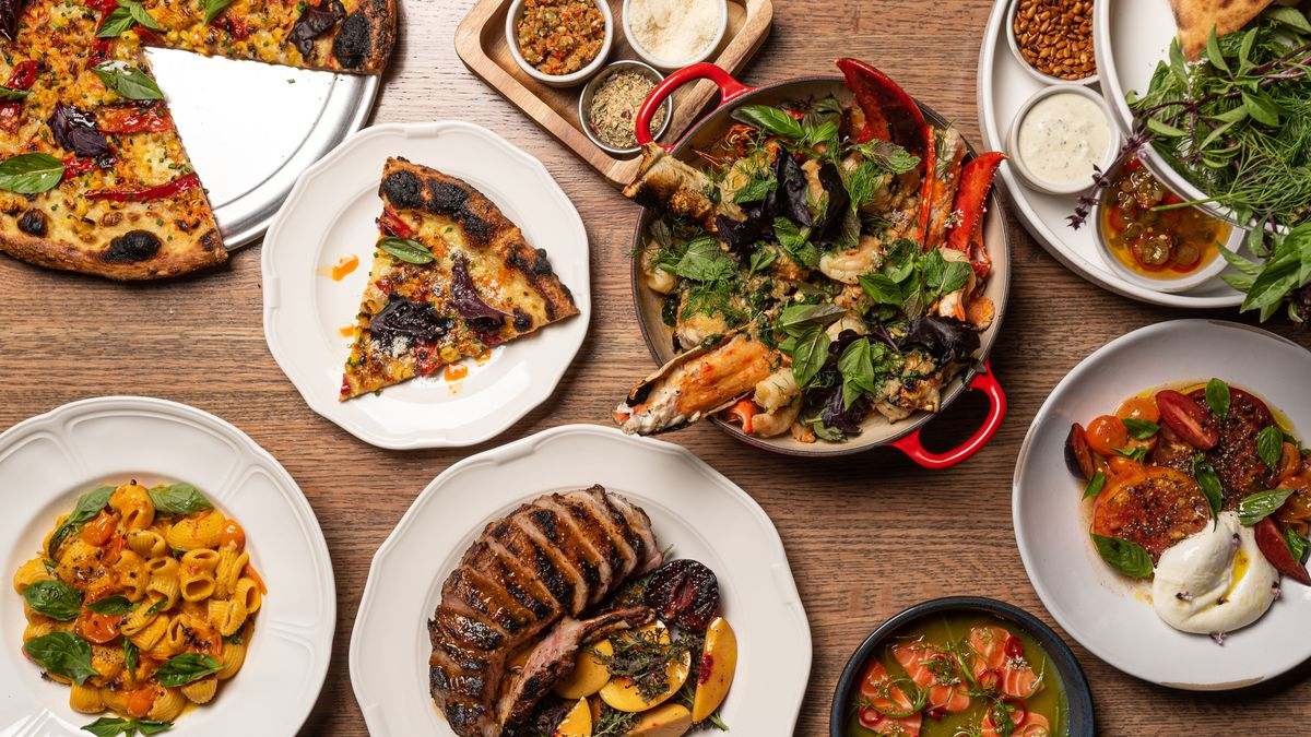 An overhead shot of round white plates holding a massive amount of Italian food on a wooden table.