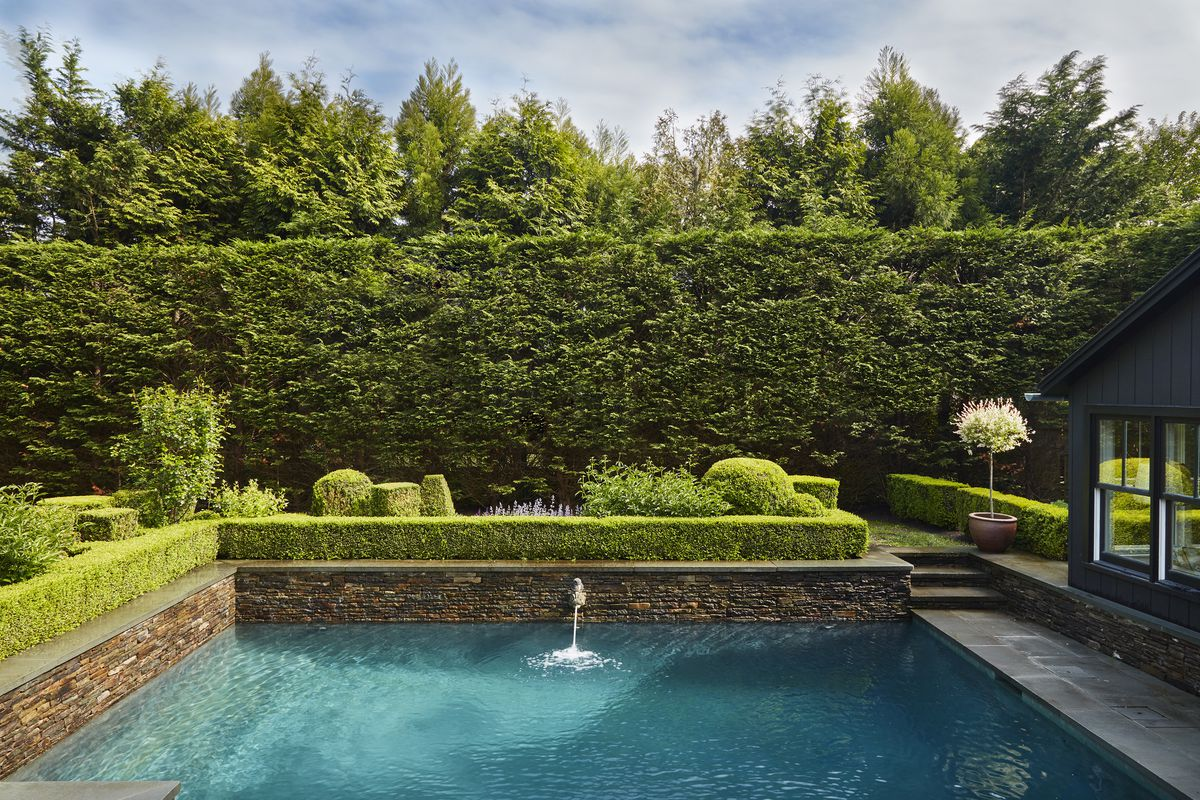 The swimming pool is surrounded by a high, lush hedge and low bushes. A wall fountain flows into the deep end.