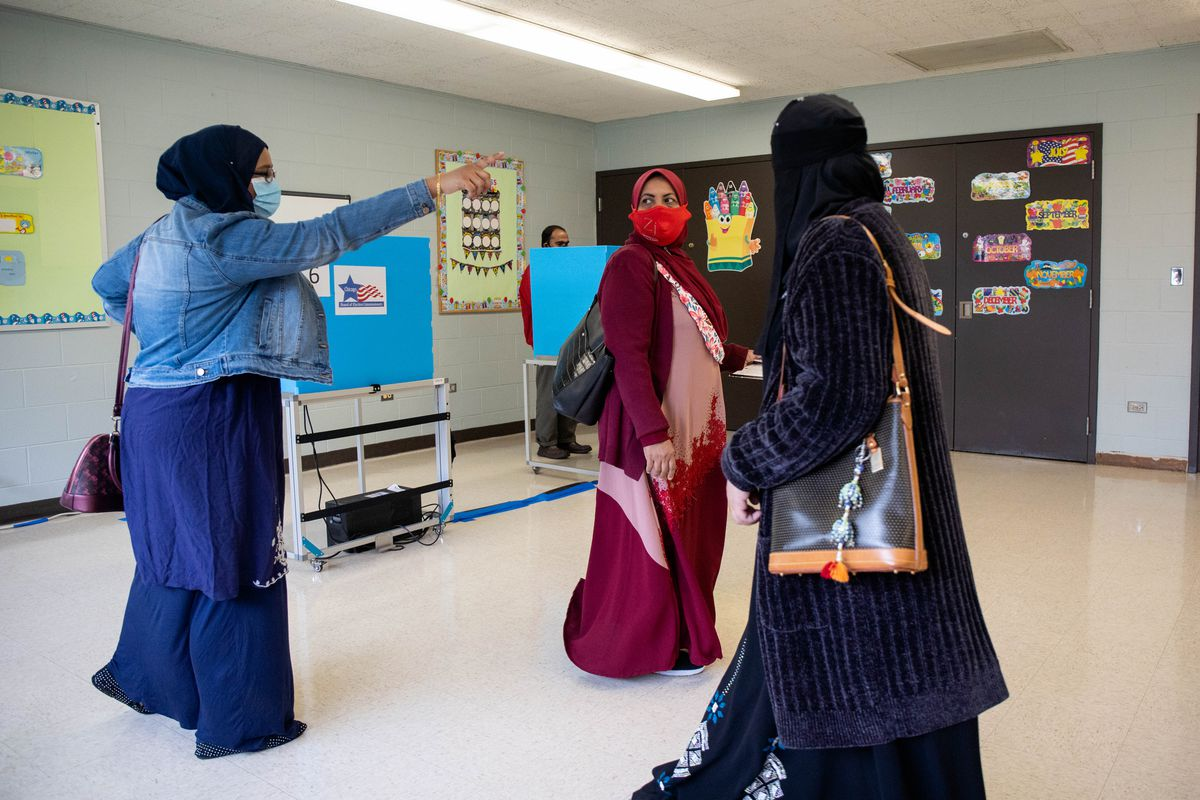 Rehana Ahmed, left, shows Bibi Sabura, center, who is voting for the first time, where to go to cast her ballot at the Warren Park Field House on Tuesday.