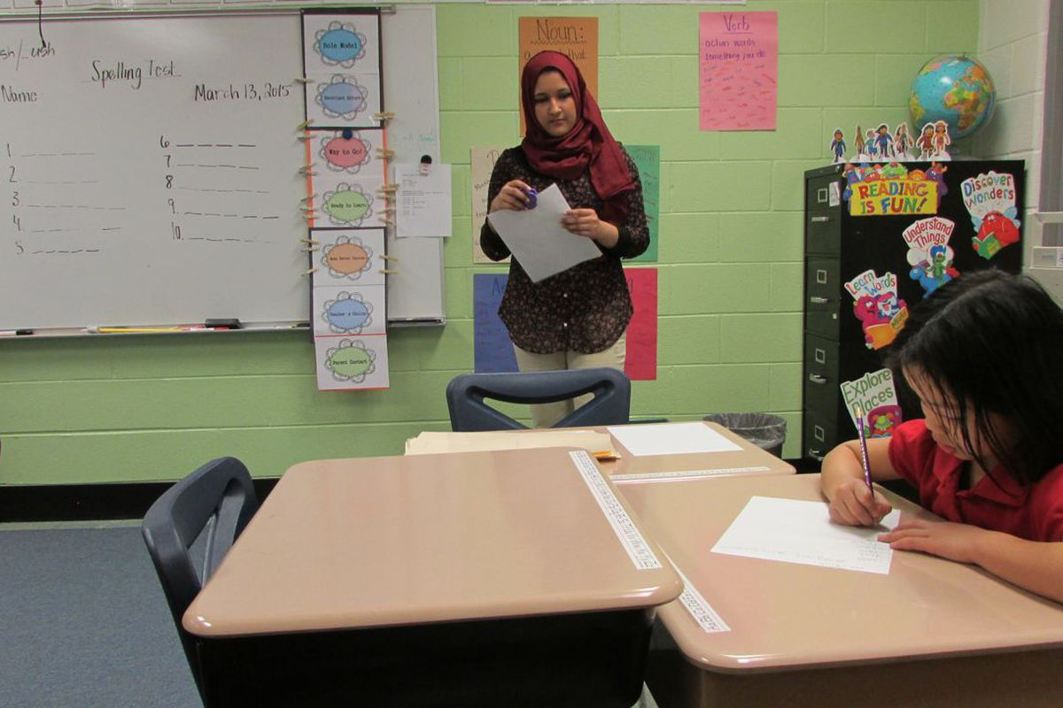 An IPS School 79 student works on a test while her teacher looks on.