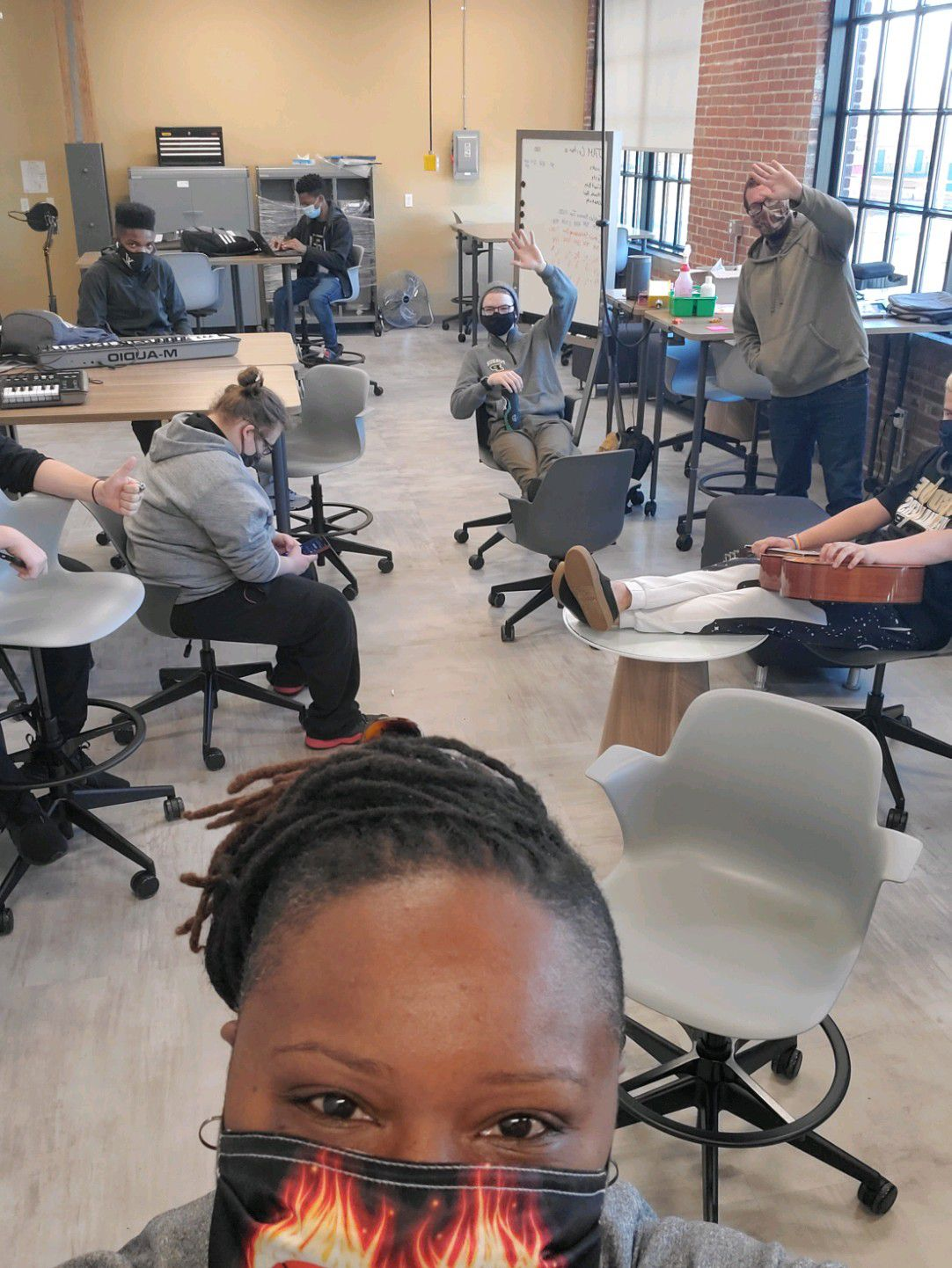Purdue Polytechnic High School Principal Shatoya Ward takes a selfie in a classroom with students waving in the background.