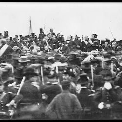 A photo of President Abraham Lincoln, hatless and seated in the center of those on the speakers platform, at the dedication of a military cemetery in Gettysburg, Pa., Nov. 19, 1863.