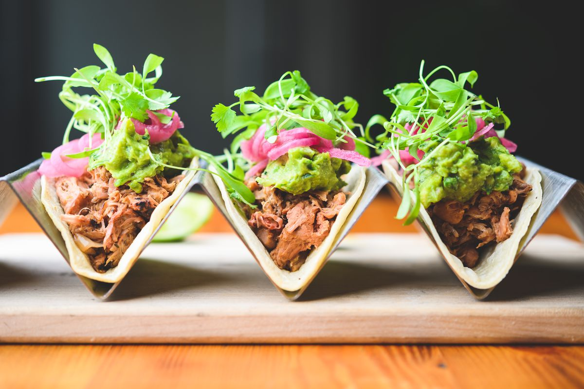 Three tacos in metal holders filled with jackfruit, pickled onions, and greens