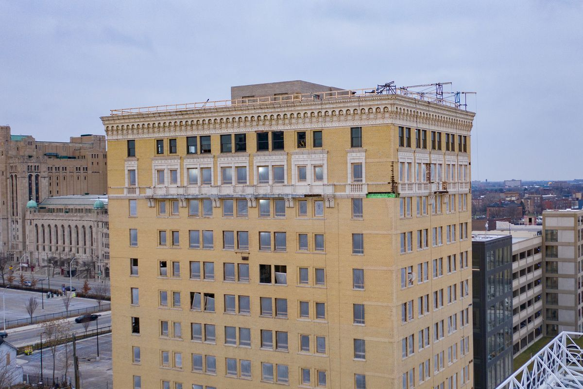The top eight floors of a cream-colored brick building. Most of the windows framed have glass installed, but some are empty or have plastic. There's a detailed terra cotta limestone cornice.