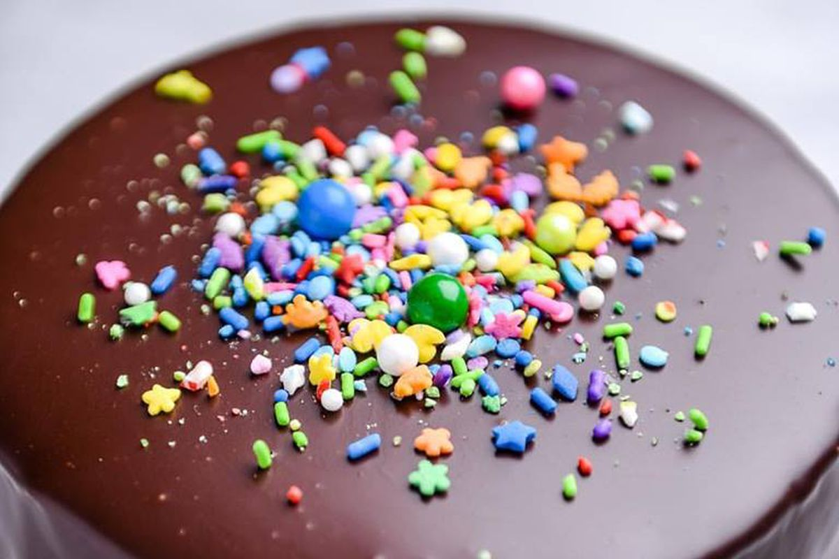 A close up of a chocolate ganache covered cake with a few sprinkles in the middle