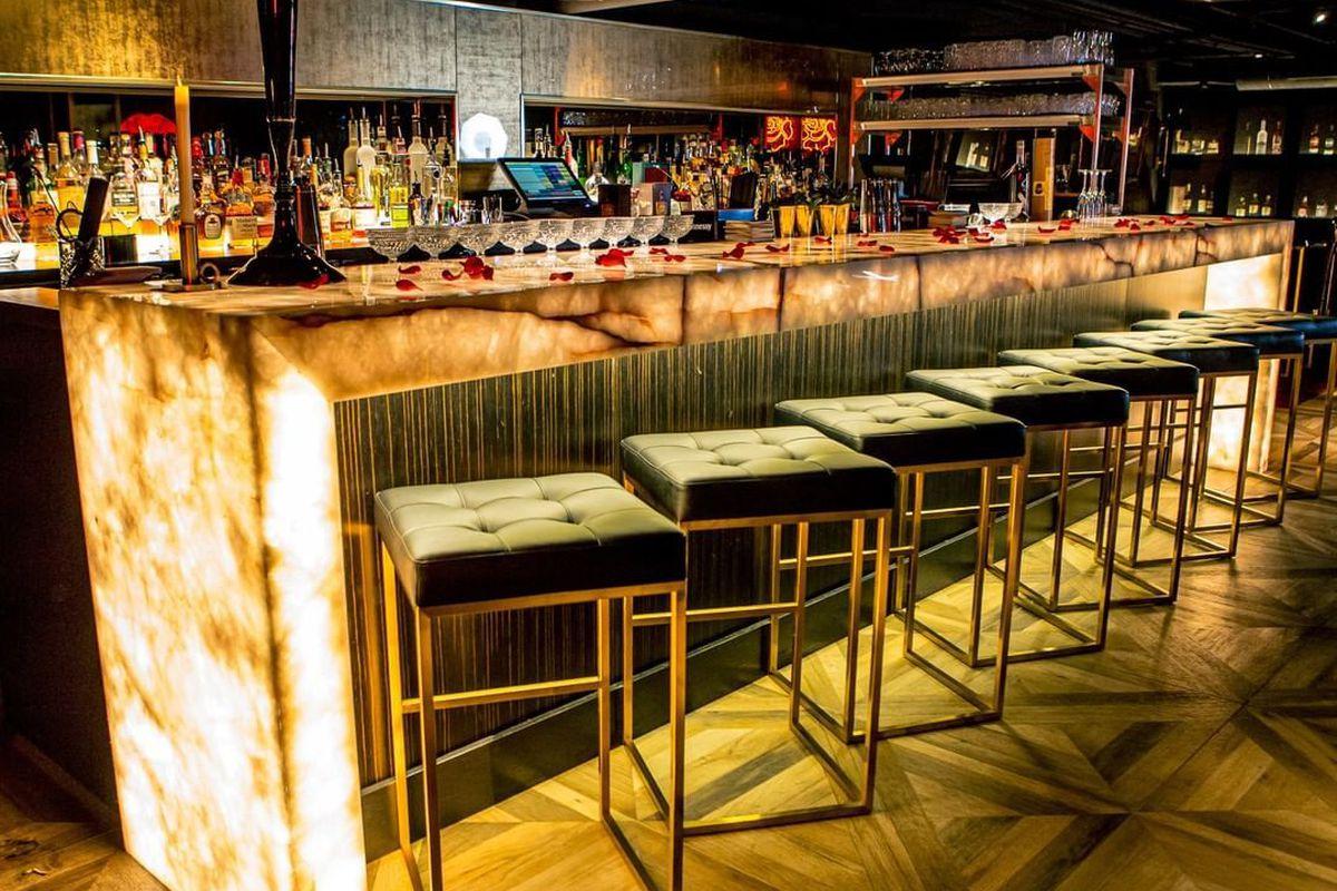 Square metal stools along a dimly lit concrete bar.