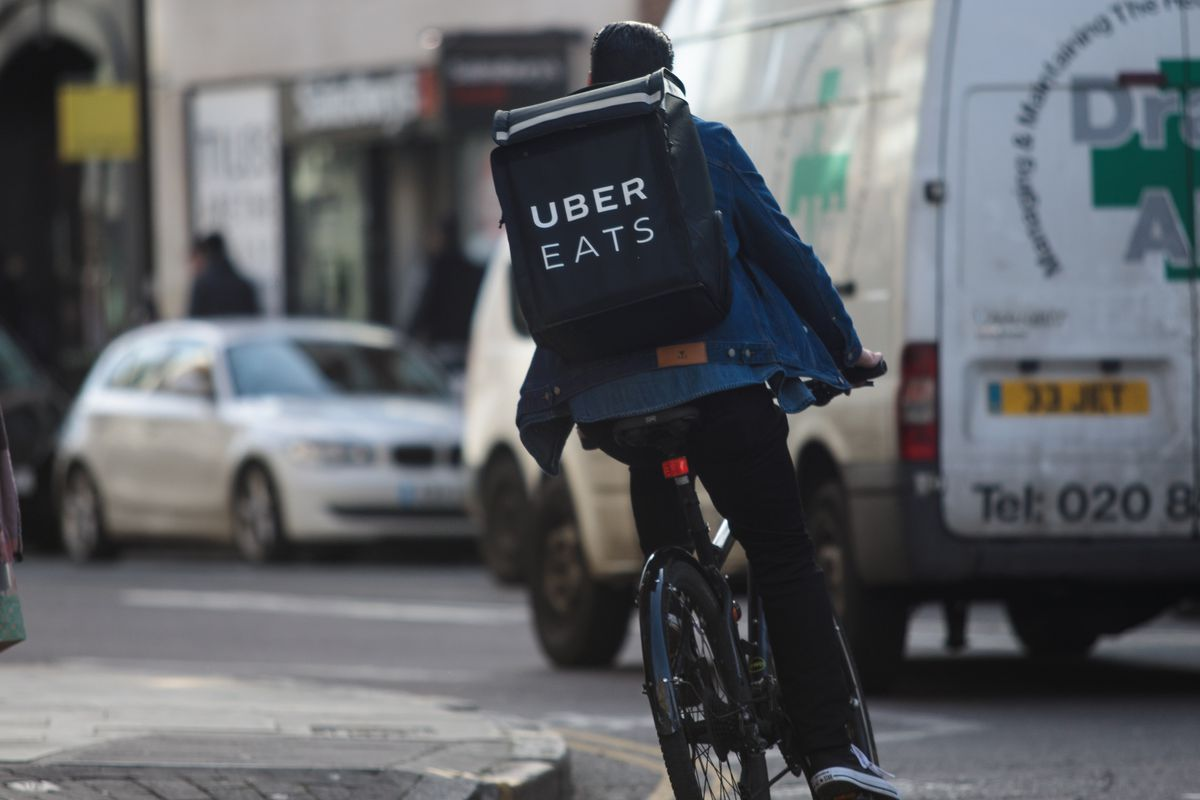 An Uber Eats bike courier rides around London with a branded rucksack