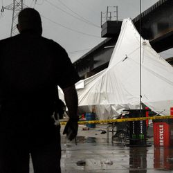 An officer from the Terminal Railroad Police Department surveys a party tent from Kilroy's Sports Bar in St. Louis as it rests against a railroad trestle near the bar after storm winds blew through the area following a baseball game between the St. Louis Cardinals and Milwaukee Brewers at nearby Busch Stadium Saturday, April 28, 2012. One person died Saturday and more than a dozen were taken to a hospital with injuries after high winds blew over a beer tent near Busch Stadium in St. Louis.