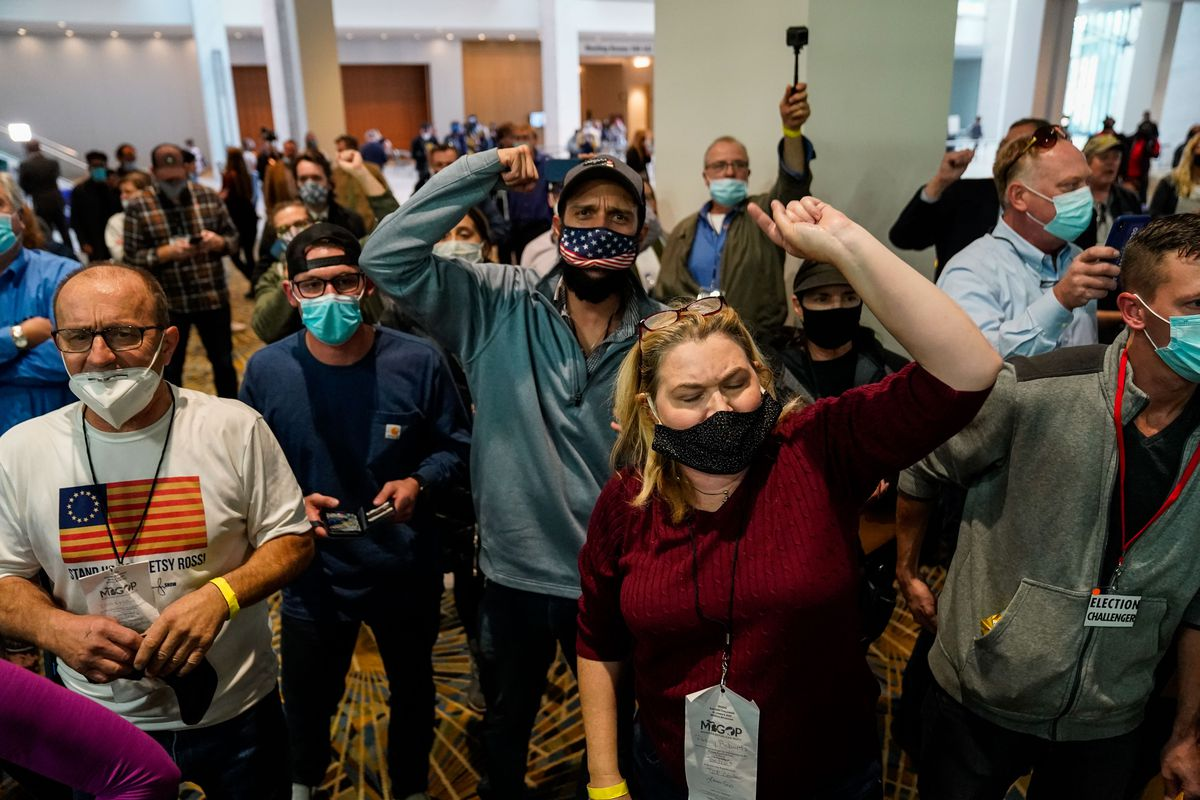 Protesters wearing masks, two with hands in the air, outside a ballot-counting facility.