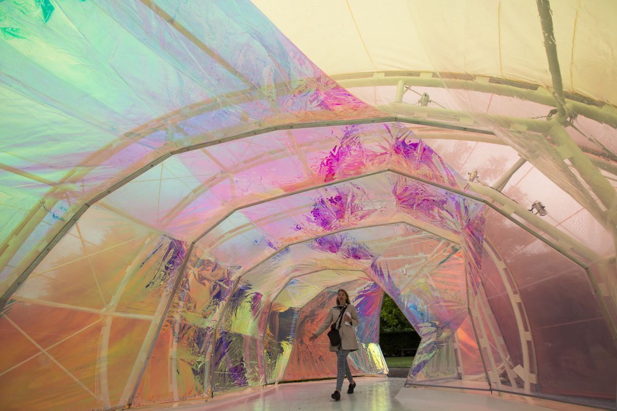 Visitors walk through the 2015 Serpentine Galleries pavilion, a colorful chrysalis structure. designed by Spanish architects Jose Selgas and Lucia Cano.