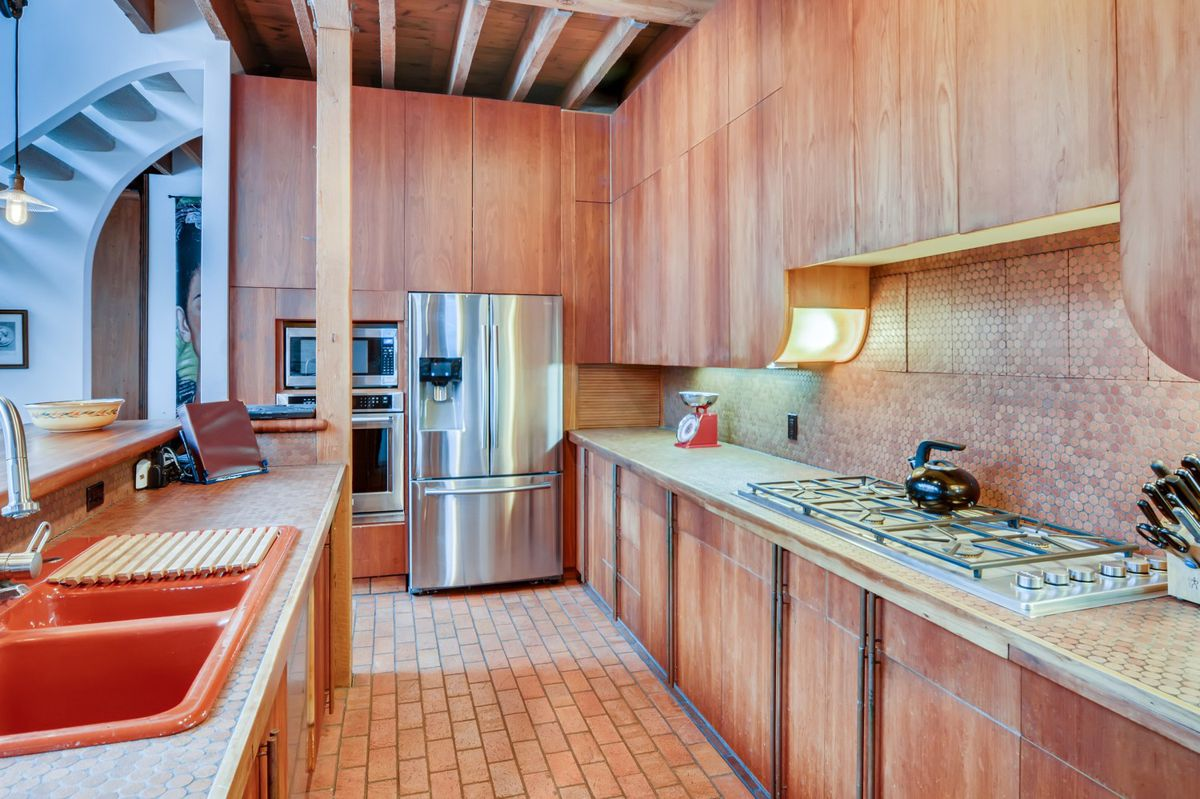 A galley kitchen has wood cabinets, an orange sink, and brick floors.